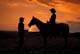 COWBOY, COWGIRL AND HORSE AT SUNSET, ST. DENIS