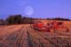 MOONRISE OVER SWATHER PARKED IN STUBBLE FIELD, LAC LA PECHE