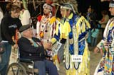 CUL NAT POW  SK  WDS05E7939DX     ABORIGINAL VETERAN IN WHEELCHAIR SHAKING HANDS WITH  POW WOW DANCERS2005 CULTURAL CELEBRATION & POW WOWSASKATOON                     ....© WAYNE SHIELS               ALL RIGHTS RESERVEDABORIGINAL;CLOTHING;CO_ED;COSTUMES;CULTURE;DANCE;DISABILITIES;ELDERS;FEMALE;FIRST;FIRST_NATIONS;GLASSES;INDOORS;MALE;NATIONS;NUMBERS;PLAINS;POW;POW_WOW;PRAIRIES;SASKATCHEWAN;SASKATOON;SENIORS;SK_;TRANSPORTATION;UNIFORMS;VETERANS;WHEELCHAIRS;WOWLONE PINE PHOTO              (306) 683-0889