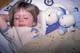 GIRL WITH STUFFED ANIMALS LAYING IN BED, SASKATOON
