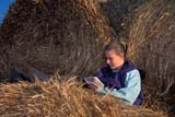FAR PEO MIS  SK     1902018D  MRGIRL READING ON ROUND BALESVANSCOY                           0411© CLARENCE W. NORRIS      ALL RIGHTS RESERVEDBALES;FARMING;GIRL;HAY;JENNIE;MR_;PEOPLE;PLAINS;PRAIRIES;QUIET;READING;RURAL;SASKATCHEWAN;SCENES;SK_;TEENS;VANSCOYLONE PINE PHOTO              (306) 683-0889