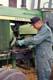 FARMER WORKING ON JOHN DEERE TRACTOR, HEPBURN