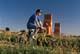 TEENAGE BOY BIKING PAST PIONEER GRAIN ELEVATOR, OSLER