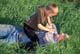 FATHER AND SON WRESTLING IN GRASS, MEADOW LAKE