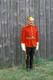 NWMP OFFICER STANDING BY STOCKADE WALL, FORT BATTLEFORD NATIONAL HISTORIC SITE