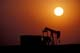 PUMP JACK, SILHOUETTED IN SETTING SUN, MANYBERRIES