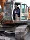 MAN IN CRANE BREAKING UP PAVEMENT ON ROAD, SASKATOON