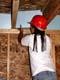 GIRL INSTALLING FOAM INSULATION IN RAFTERS, SASKATOON