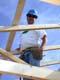 MAN STANDING IN ROOF RAFTERS, SASKATOON