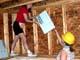 WOMEN PUTTING INSULATION BETWEEN FLOOR JOISTS, SASKATOON