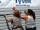WOMEN APPLYING VINYL SIDING OVER TYVEK HOMEWRAP, SASKATOON