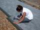 WOMAN SHINGLING HOUSE, SASKATOON