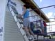WOMAN ON LADDER INSTALLING VINYL SIDING, SASKATOON