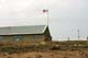 NUNAVUT FLAG AND BUILDING WITH STEEL ROOF, CAMBRIDGE BAY