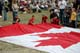 PEOPLE WITH CANADIAN FLAG, CANADA REMEMBERS AIRSHOW, SASKATOON