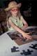 CHILD WORKING ON JIGSAW PUZZLE, SASKATOON