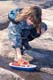 GIRL PLAYING WITH PLASTIC BOAT IN SPRING, SASKATOON
