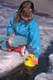 GIRL PLAYING WITH PLASTIC DUCK IN SPRING, SASKATOON
