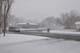 VAN AND BICYCLIST ON STREET DURING APRIL SNOWSTORM, WARMAN