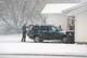 MAN LOADING SUV DURING APRIL SNOWSTORM, WARMAN