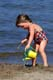 GIRL ON BEACH USING WATERING CAN, EMMA LAKE