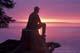 MAN SITTING ON LAKESHORE AT SUNSET, PRINCE ALBERT NATIONAL PARK