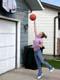 GIRL PLAYING BASKETBALL IN FRONT OF HOUSE, SASKATOON