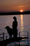 PEO ACT SUM  SK   WS21398D  VTGIRL AND DOG ON DOCK AT SUNSETMEADOW LAKE PROV PK    07© WAYNE SHIELS                ALL RIGHTS RESERVEDACTIVITIES;ANIMALS;BULLETINS;DOCKS;DOGS;FRIENDS;LAKES;MEADOW_LAKE_PP;OUTDOORS;PARKLAND;PEOPLE;PETS;PP_;RECREATION;SASKATCHEWAN;SILHOUETTE;SK_;SUMMER;SUNSETS;VTL;WATERLONE PINE PHOTO              (306) 683-0889