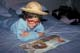 FEMALE YOUTH READING ON BED WEARING WIG, RED GLASSES & STRAW HAT, SASKATOON