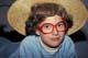 FEMALE YOUTH WEARING WIG, RED GLASSES & STRAW HAT, SASKATOON