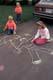 YOUNG GIRL MAKING CHALK DRAWINGS ON PAVEMENT, SASKATOON