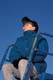 GIRL ON TOP OF SLIDE IN WINTER BLOWING BUBBLES, SASKATOON