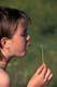 GIRL BLOWING DANDELION SEEDS, PIKE LAKE PROVINCIAL PARK
