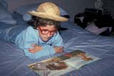 PEO YOU MIS  SK     1404501D  MRFEMALE YOUTH READING ON BED WEARING WIG, RED GLASSES & STRAW HATSASKATOON                       03                  © CLARENCE W. NORRIS      ALL RIGHTS RESERVEDACTIVITIES;BOOKS;CHILDREN;CLOTHING;COSTUMES;FEMALE;FUN;GLASSES;HATS;INDOORS;JENNIE;MR_;PEOPLE;PLAINS;PRAIRIES;READING;RECREATION;SASKATCHEWAN;SASKATOON;SK_;SPRING;WIGSLONE PINE PHOTO              (306) 683-0889
