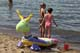 CHILDREN AND INFLATABLE TOYS ON BEACH, WASKESIU LAKE, PRINCE ALBERT NATIONAL PARK