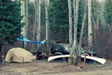 REC CAM MIS  SK     1102810AD               CAMPSITE, CANOE AND 4X4 IN SPRINGPIPRELL LAKE                      05/..© CLARENCE W. NORRIS      ALL RIGHTS RESERVEDACTIVITIES;AUTOS;BOREAL;CAMPING;CANOEING;OUTDOORS;PIPRELL_LAKE;RECREATION;SASKATCHEWAN;SHELTERS;SK_;SPRING;TENTS;TREESLONE PINE PHOTO              (306) 683-0889