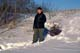 MAN PULLING FIREWOOD ON TOBOGGAN AT WINTER CAMP, WAKAW