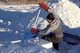 MAN CUTTING SNOW BLOCKS AT WINTER CAMP, WAKAW