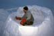 MAN BUILDING IGLOO AT WINTER CAMP, WAKAW