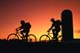 TEENAGE BOY AND GIRL BICYCLING AT SUNSET PAST SILO, OSLER