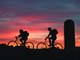 BOY AND GIRL BICYCLING AT SUNSET BY SILOS, OSLER