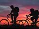 BOY AND GIRL BICYCLING AT SUNSET, OSLER