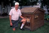 REC WOO CAR  SK     1803313D  MR #302  WOOD CARVER WITH CARVED HEAD OF DOG SHASTASASKATOON                       07/06© CLARENCE W. NORRIS      ALL RIGHTS RESERVEDANIMALS;CARVING;DOGHOUSES;DOGS;HOBBIES;MALE;MR_;PEOPLE;PLAINS;PRAIRIES;RECREATION;SASKATCHEWAN;SASKATOON;SK_;SUMMER;WOOD;WOOD_CARVINGSLONE PINE PHOTO              (306) 683-0889