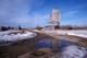 SASKATCHEWAN WHEAT POOL ELEVATOR REFLECTED IN SPRING WATER PUDDLES, PADDOCKWOOD